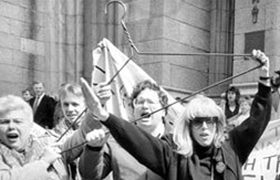 Merle Hoffman raises her trademark hanger outside St Patricks Cathedral in New York in 1989. Photograph: Courtesy of Merle Hoffman