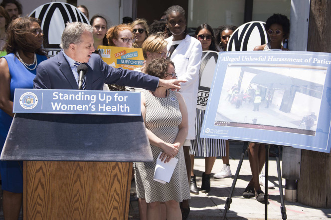 New York Attorney General Eric Schneiderman points to a poster showing alleged harassment outside the Queens clinic. Dennis A. Clark