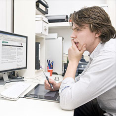 Man sitting at office desk looking at computer